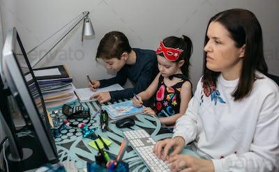 Woman teleworking with her children doing homework