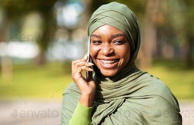 Black Muslim Woman Talking On Mobile Phone Standing Outdoors