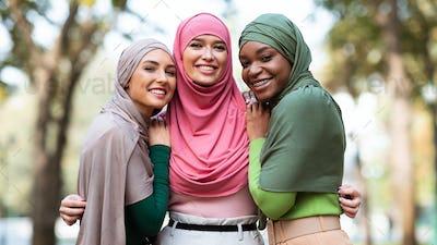 Three Muslim Women In Hijab Posing Hugging Outdoors, Panorama