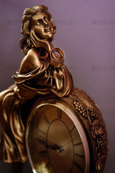 stylish pair of golden wedding ring on metal gold woman figurine with clock, time concept