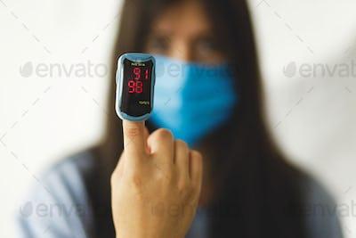 Detecting coronavirus at home, injury lungs and pneumonia by virus. Pulse Oximeter on hand