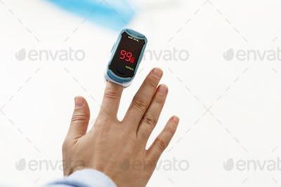 Pulse Oximeter on finger, measuring blood oxygen level, detecting coronavirus pneumonia