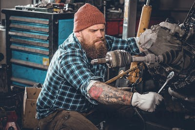 Bearded male repairing car's engine in a garage.