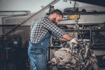 A man repairing the car's engine.