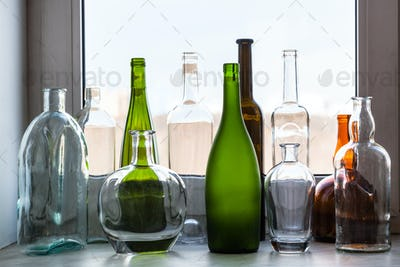 various empty bottles on sill of home window