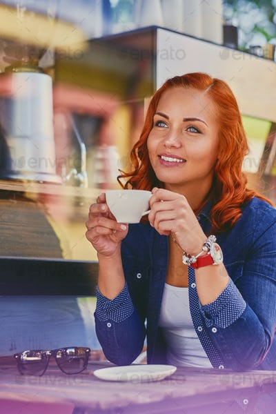 Portrait of redhead female drinks coffee in a cafe.