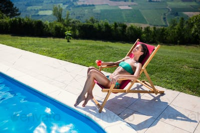 Woman relaxing and sun tanning by the swimming pool