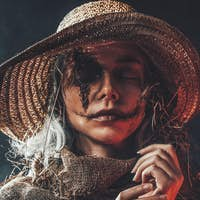 Woman with scars and straw hat in dark background