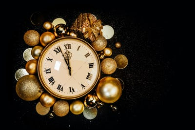 Gold clock on a black shiny background, the coming of a Happy New Year.