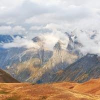 Fantastic snow-capped mountains in the beautiful cumulus clouds. Main Caucasian Ridge. Type Mount