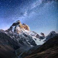 Fantastic starry sky. Autumn landscape and snow-capped peaks. Main Caucasian Ridge. Mountain View