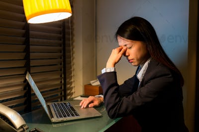 Business woman feeling headache when working at night