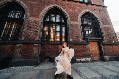 A bride in a wedding dress with long hair in the old town of Wroclaw. Wedding photo shoot in the