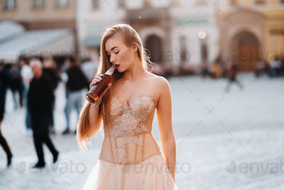 A bride in a wedding dress with long hair and a drink bottle in the Old town of Wroclaw. Wedding
