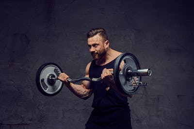 Huge bearded bodybuilder working out with barbells.