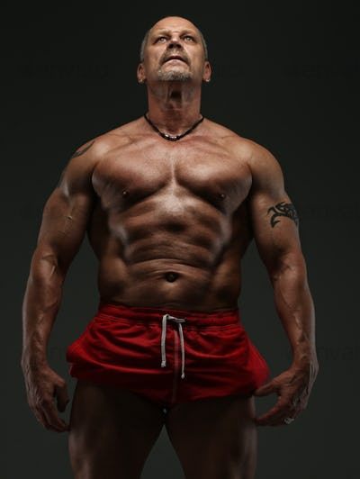 Muscular middle age man showing his muscules