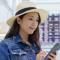 Woman use of mobile phone inside airport