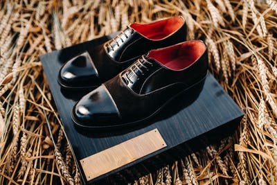 Classic black men's shoes are in the field on what.Shoes are on the box