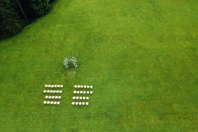 Top view of the wedding venue in a green field. Wedding ceremony with decorated decor on a green