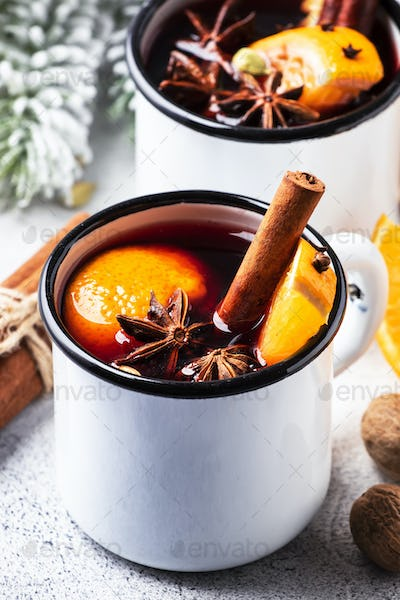 Mulled wine in white metal mugs with cinnamon, spices and orange on gray