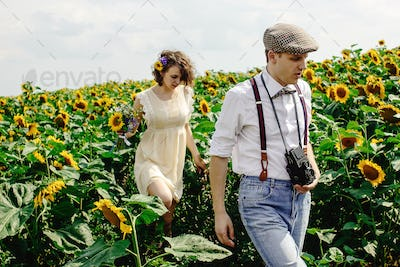 beautiful gorgeous bride and stylish handsome groom, rustic couple in a sunflower sunny field