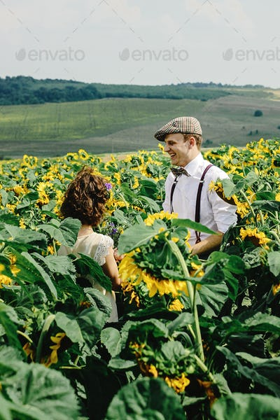 beautiful gorgeous bride and stylish handsome groom, rustic couple having fun in a sunflower field