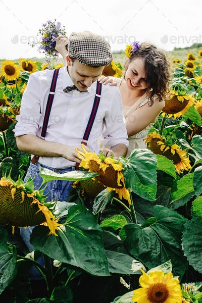 beautiful gorgeous bride and stylish handsome groom, joyful rustic couple in a sunflower field