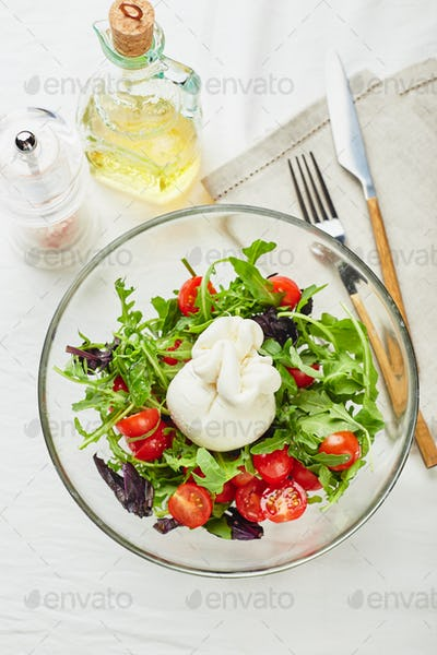 Burrata, Italian fresh cheese made from cream and buffalo or cow milk, with tomato, arugula