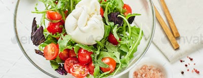 Burrata, Italian fresh cheese made from cream and buffalo or cow milk, with salad