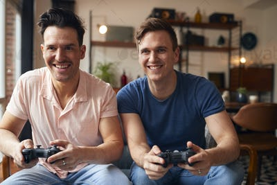 Loving Same Sex Male Couple Sitting On Sofa At Home Gaming Together