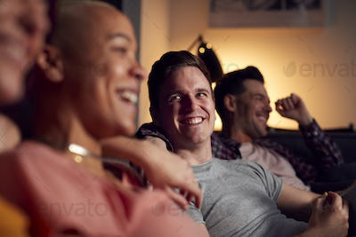 Group Of Gay Friends Sitting On Sofa At Home Watching Evening TV And Relaxing Together