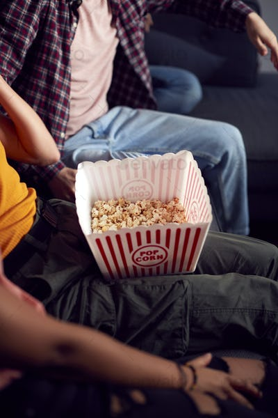 Close Up Of Gay Friends Sitting On Sofa At Home Eating Popcorn And Watching TV Together