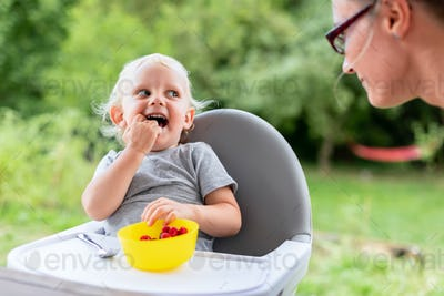 Mother and her baby son eating together outdoor and have fun
