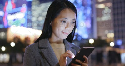 Businesswoman use of mobile phone in city at night