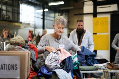 Volunteers sorting out donated clothes in community charity donation center.