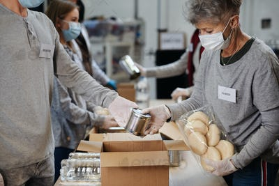 Group of volunteers in community donation center, food bank and coronavirus concept.