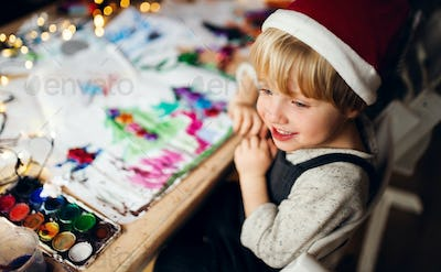 Top view of small boy indoors at home at Christmas, painting pictures.