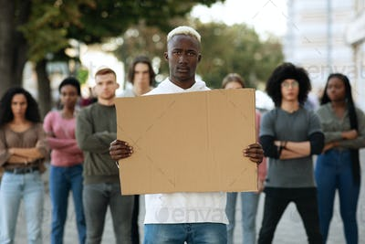 African american guy with empty placard leading group of protestors