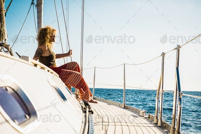 Young beautiful girl lay down and relax on a sail boat