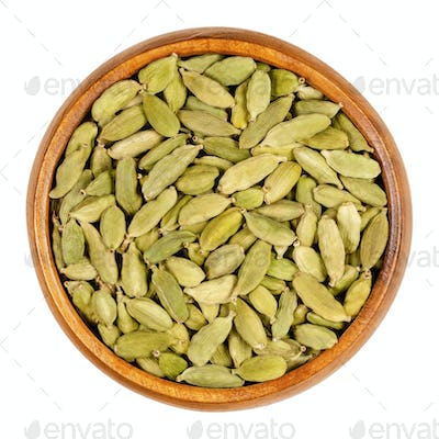 Green cardamom pods, processed true cardamom seeds, in a wooden bowl