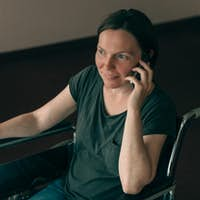 Hopeful female person with disability talking on mobile phone