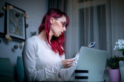 Stressed shocked woman checking financial documents using calculator and laptop until late at night
