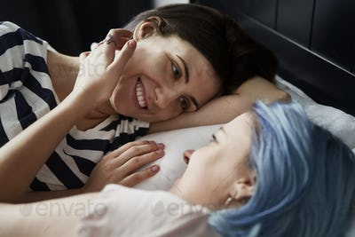 Close up of happy lesbian couple lying on bed