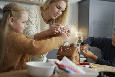 Image of family spending Christmas time on decorating gingerbread house