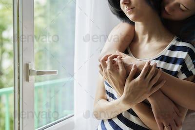 Unrecognizable lesbian couple in tender embrace
