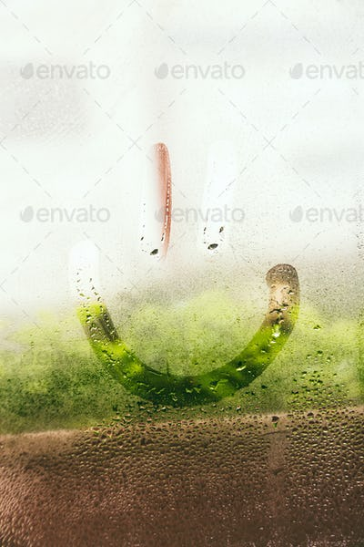 Smiley face hand drawing in a wet window