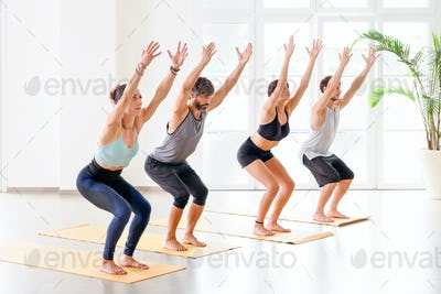 Group of people doing Utkatasana or Chair pose