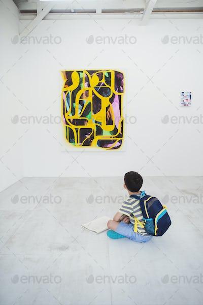 Boy sitting on floor in art gallery looking at modern painting.