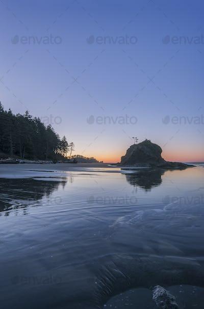 Sunrise horizon behind rock formations on beach