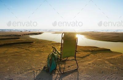 Lounge chair on beach under blue sky